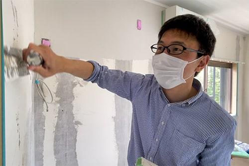 コテをつかって壁を塗るイメージ